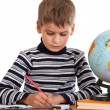 Cute schoolboy is writting — Stockfoto