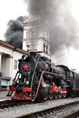 Old steam train is leaving a station — Stock Photo