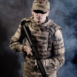 Soldier with a rifle on a black background - Stock Photo