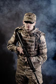 Soldier with a rifle on a black background — Stock Photo