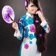 Beautiful asian woman wears a national dress is holding a fan — Stock Photo