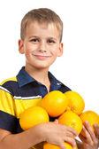 Pojke anläggning apelsiner — Stockfoto