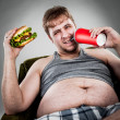 Fat man eating hamburger - Stock Photo