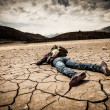 Person lays on the dried ground — Stock Photo