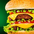 Tasty and appetizing hamburger on a darkly green — Stock Photo