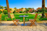 Resort and small lawn with chairs early morning. — Stock Photo