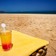 Glass of juice next to beach. - Stock Photo