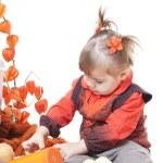 Little girl in an orange vest plays with big pumpkins — Stock Photo