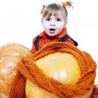 Little girl in an orange vest plays with big pumpkins — Stock Photo