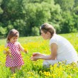 Mother with the small daughter play on a glade with dandelions — Stock Photo #11323155