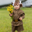 Little girl in a military uniform with wild flowers in a hand — Stock Photo
