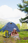 Girl has a rest in green tent against mountains — Stock Photo