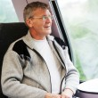 Stock Photo: Smiling mgoes in train and looks out of window