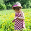 Little girl in a hat on a glade with dandelions — Stock Photo
