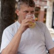 Mature man drinks beer in street cafe — Stock Photo