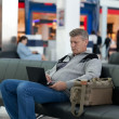 Passenger waiting for flight works at the laptop — Stock Photo
