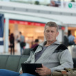 Male traveler with laptop uses Wi-Fi with expectation of flight — Stock Photo #11967141