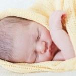 dormir bebé envuelto en una manta amarilla — Foto de Stock