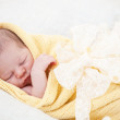 Sleeping newborn baby wrapped in a yellow blanket — Stock Photo #11967285