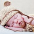 Sleeping newborn baby with a ridiculous knitted hat — Stock Photo #11967307
