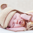 Sleeping newborn baby with a ridiculous knitted hat — Stock Photo #11967310
