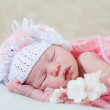 Newborn girl sleeps with spring flowers under a knitted pink cape — Stock Photo #11967328