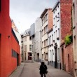 Cyclist goes on the ancient narrow street in the Belgian city of Malines (Mechelen) - Stock Photo