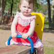 Little girl shakes on a swing in park - Stock Photo
