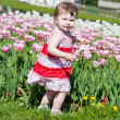Little girl in an elegant sundress in city park on walk - Stock Photo