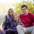 Happy parents with the daughter on walk in autumn park — Stock Photo