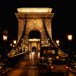 Chain bridge at night with cars - Stock Photo