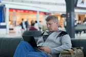 Mature man with the laptop in a hall expectation of the international airport — Stock Photo