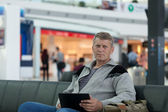 Male traveler with the laptop uses a Wi-Fi with expectation of the flight — Stock Photo