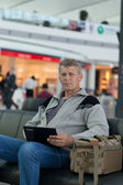 Man the passenger with the laptop in a waiting room of the modern station — Stock Photo