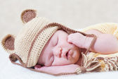 Sleeping newborn baby with a ridiculous knitted hat — Stock Photo
