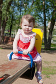 Little girl shakes on a swing in park — Stock Photo