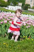 Little girl in an elegant sundress in city park on walk — Stock Photo