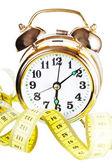 Alarm clock and measuring tape — Stock Photo