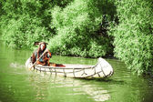 North American Indian floats down the river on a canoe — Stock Photo
