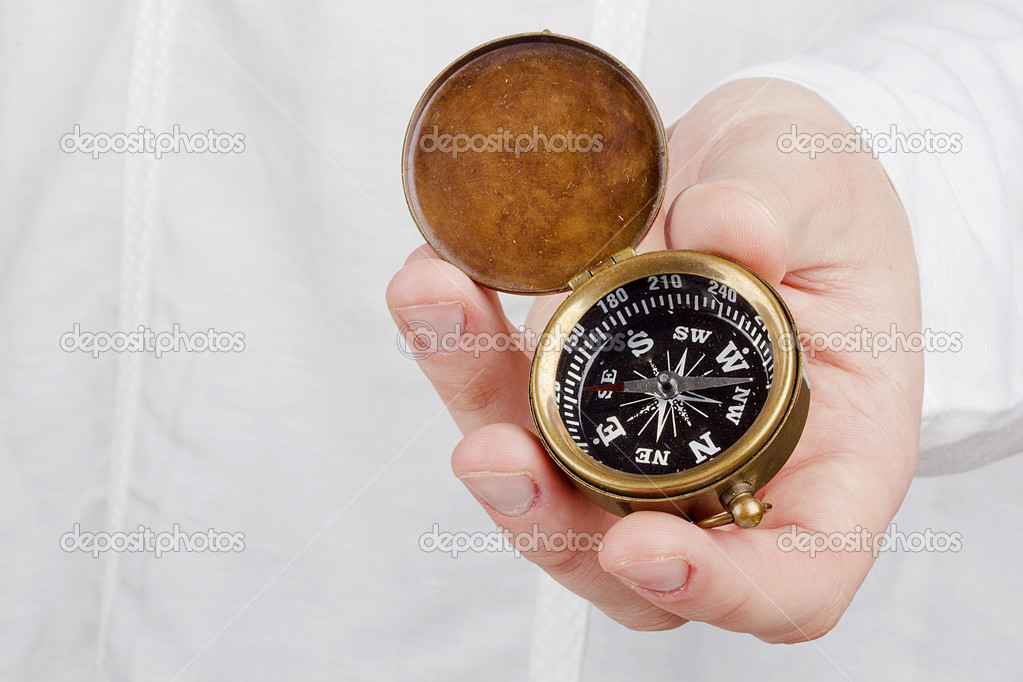 Close-up photograph of a hand holding an old compass.  Stock Photo #11633351