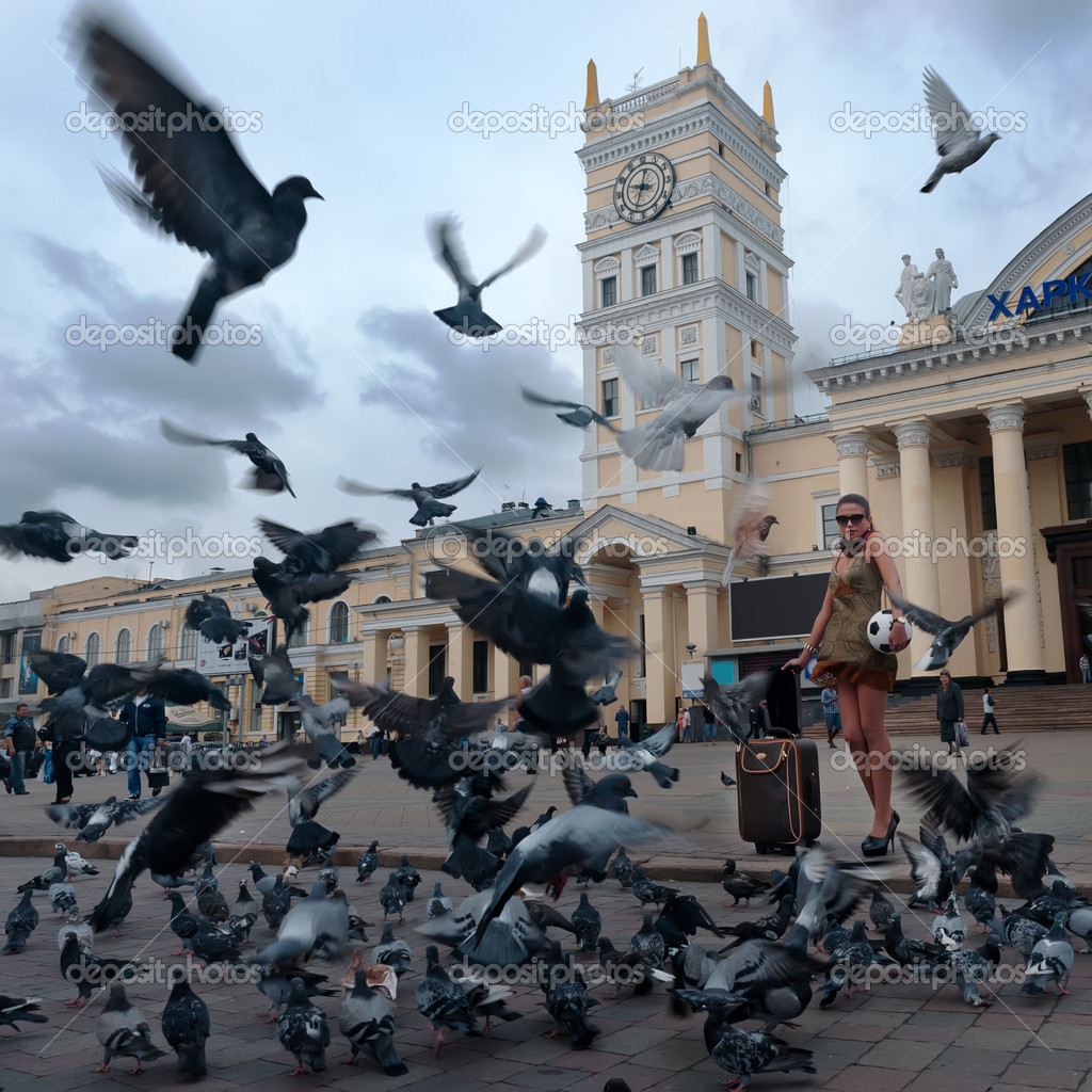 Photo of girl-traveller surrounded flock of birds in the square — Stock Photo #11593769