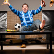 Soccer fan on sofa - Stock Photo