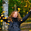 Stock Photo: Happy woman is throwing dry autumn leaves in park