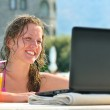 Woman is using laptop from swimming pool near the hotel — Stock Photo