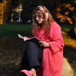 Stock Photo: Happy womis reading magazine at forest in undress