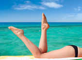 Sexy female legs against turquoise sea — Stock Photo