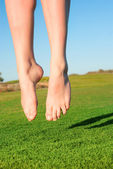 Closeup of feet of jumping on green field woman — Stock Photo
