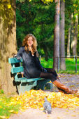 Young woman is sitting on the bench in autumn park and looking a — Stock Photo
