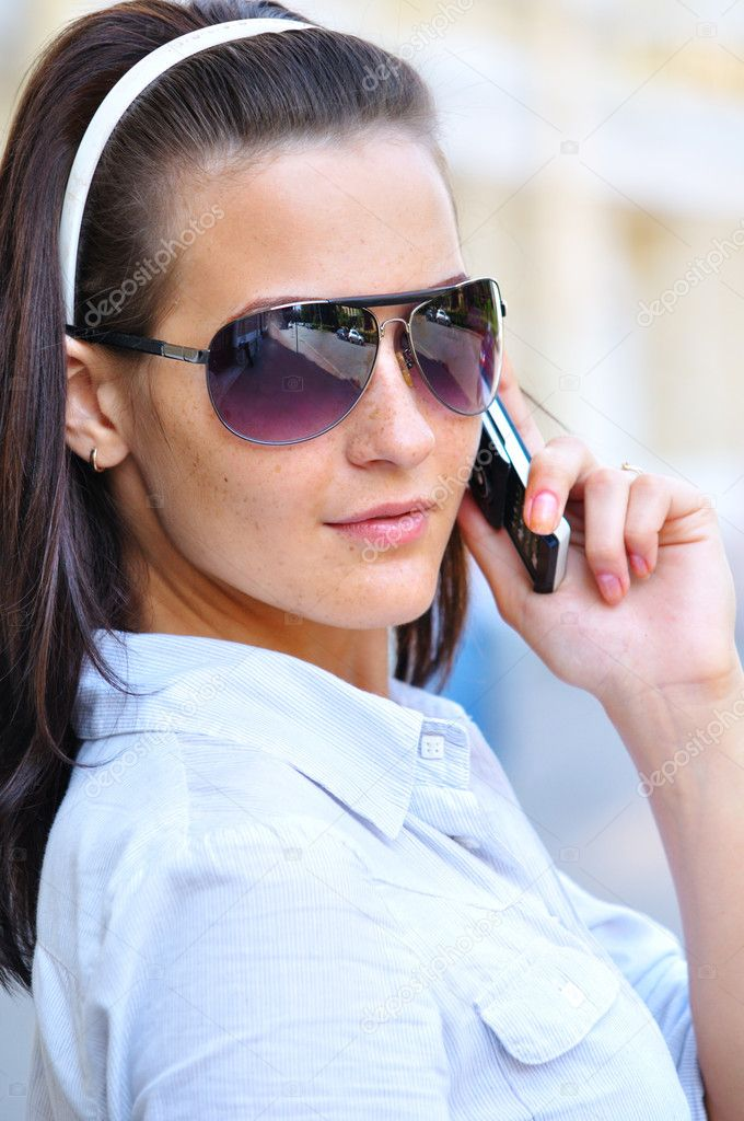 Strict woman is looking back and talking phone — Stock Photo #10788085