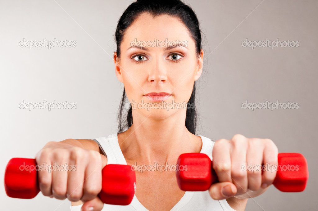 Sporty woman is holding two red barbells on grey background and looking at camera — Stock Photo #10802103
